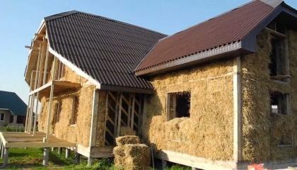 Будинок зі соломи: за технологією, спочатку готується дерев'яний каркас, а потім гідравлічним пресом в нього пресується солома. Після цього вона обстригається, і виходить рівна панель